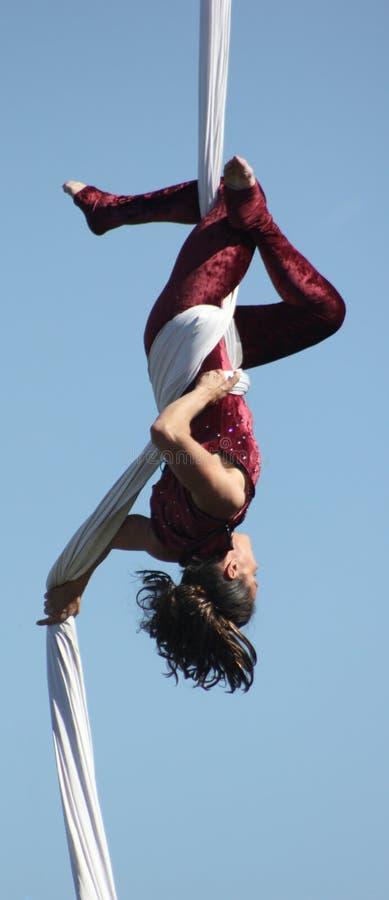 Le bel acrobate féminin exécute sur des soies photographie stock libre de droits