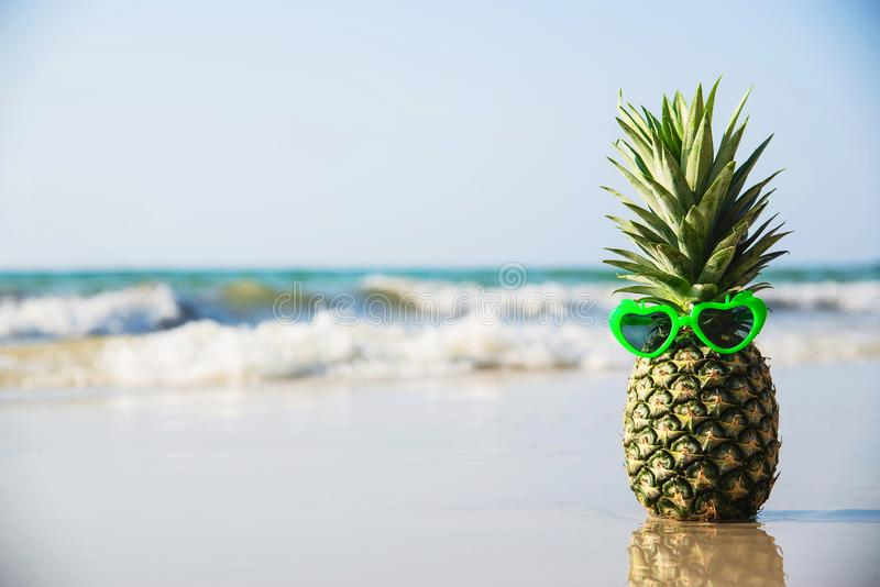 Le bel ananas frais a mis des verres de soleil de forme de coeur sur la plage propre de sable avec le fond de vague de mer photos libres de droits