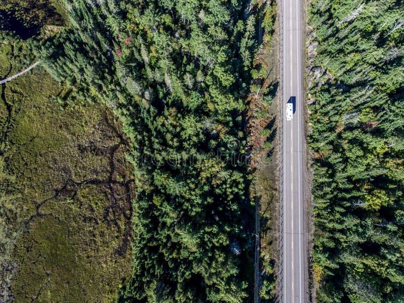 Le bel autobus de campeur de Canada conduisant sur la forêt sans fin de pin de route avec des lacs amarrent le fond de voyage de  image libre de droits