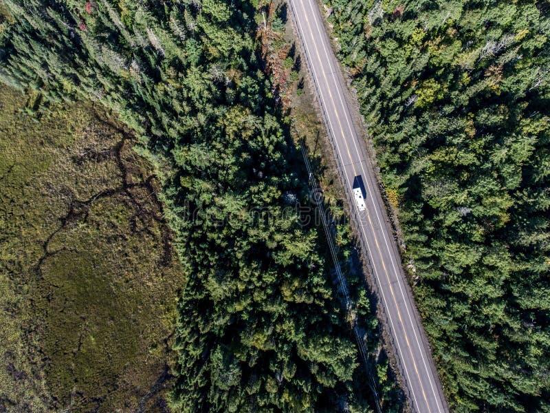 Le bel autobus de campeur de Canada conduisant sur la forêt sans fin de pin de route avec des lacs amarrent le fond de voyage de  photographie stock