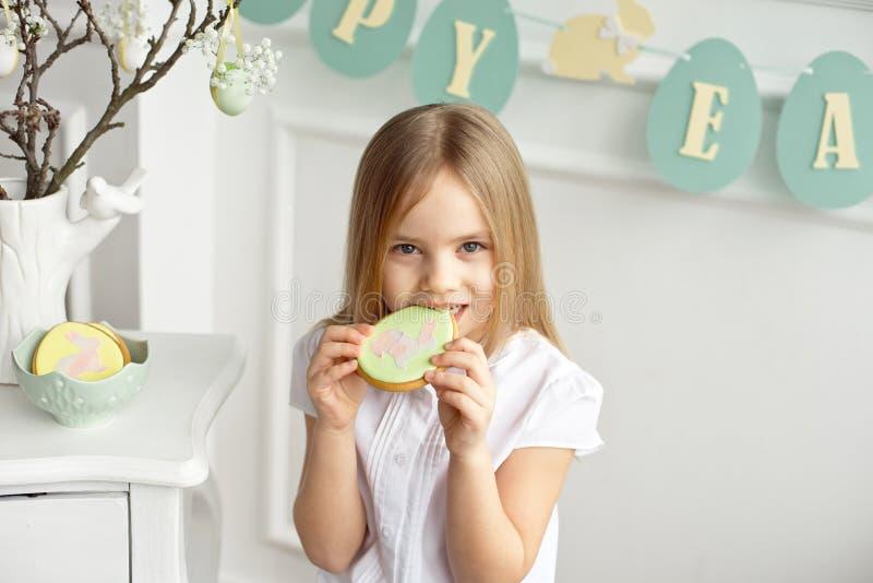 Le bel enfant mange des oeufs de pain d'épice Famille heureuse se préparant à Pâques image libre de droits