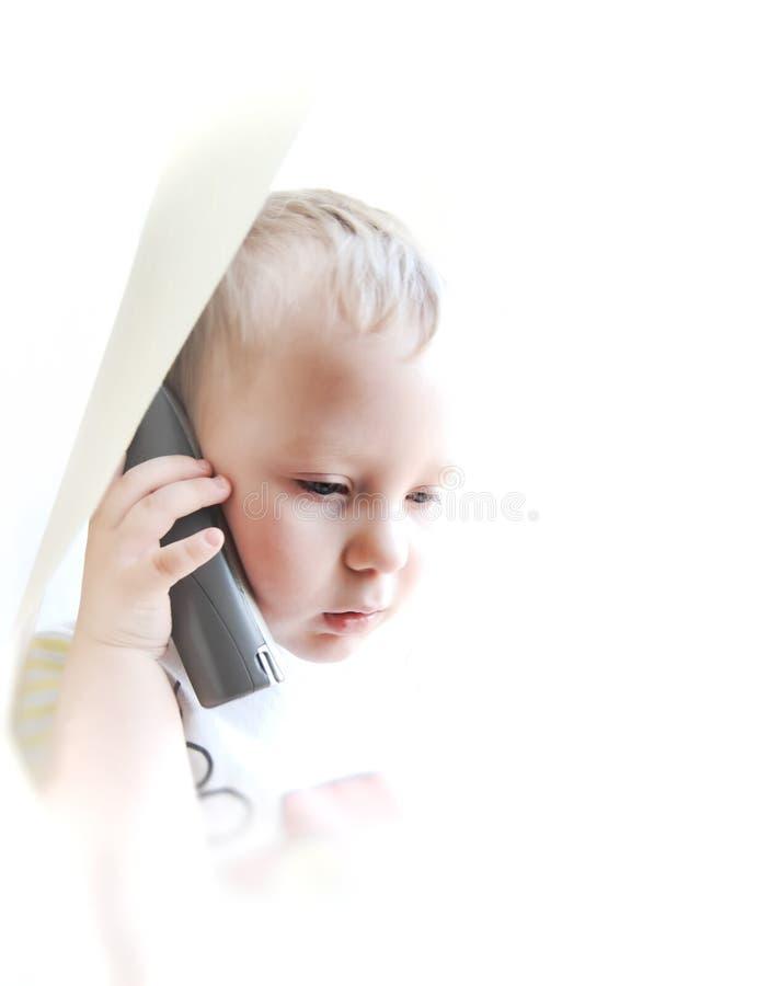Le bel enfant parlant par le téléphone image stock