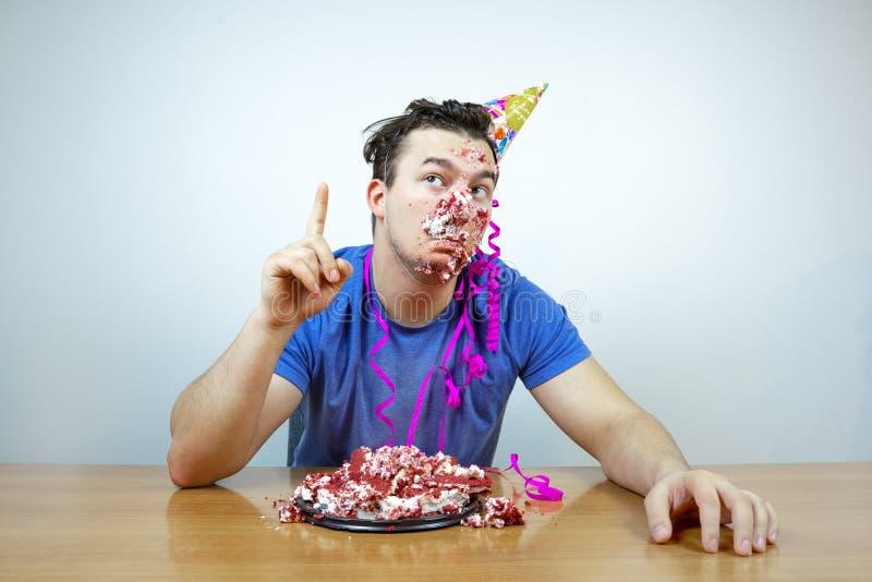Le bel homme caucasien émotif avec le chapeau de cône de fête d'anniversaire sur la tête et chiffonnent le gâteau soulève votre i image libre de droits
