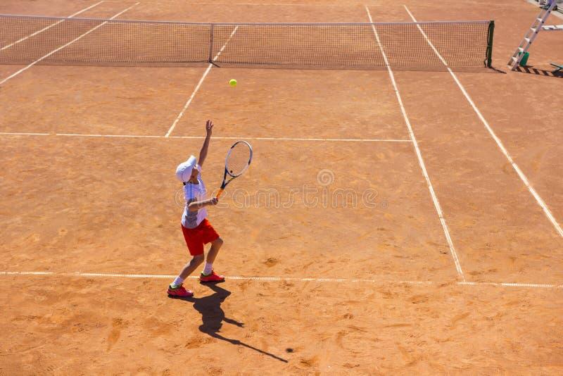 Le Belarus, Minsk 26 05 18 Le garçon joue au tennis sur la cour orange de saleté Cour dur photographie stock