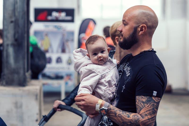 Le Belarus, Minsk, peut 17, 2015, rue d'Oktyabrskaya, festival de cycliste cycliste d'homme avec sa petite position de fils sur u image stock