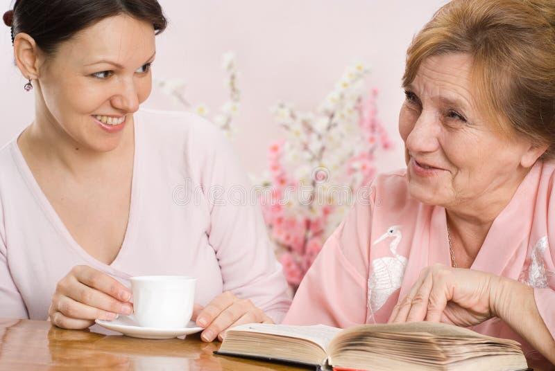 Le belle donne adulte si siedono e comunicano immagine stock libera da diritti