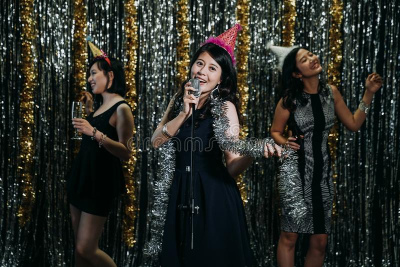 Le belle donne asiatiche amano la musica godono del karaoke fotografia stock