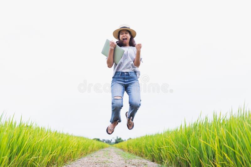 Le belle donne asiatiche sono felici e saltanti nel giacimento del riso e stanno tenendo un modello del computer portatile immagini stock