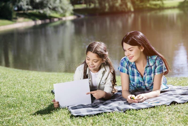 Le belle e ragazze piacevoli stanno trovando sulla coperta su erba La donna sta giudicando le matite variopinte disponibile La ra immagine stock