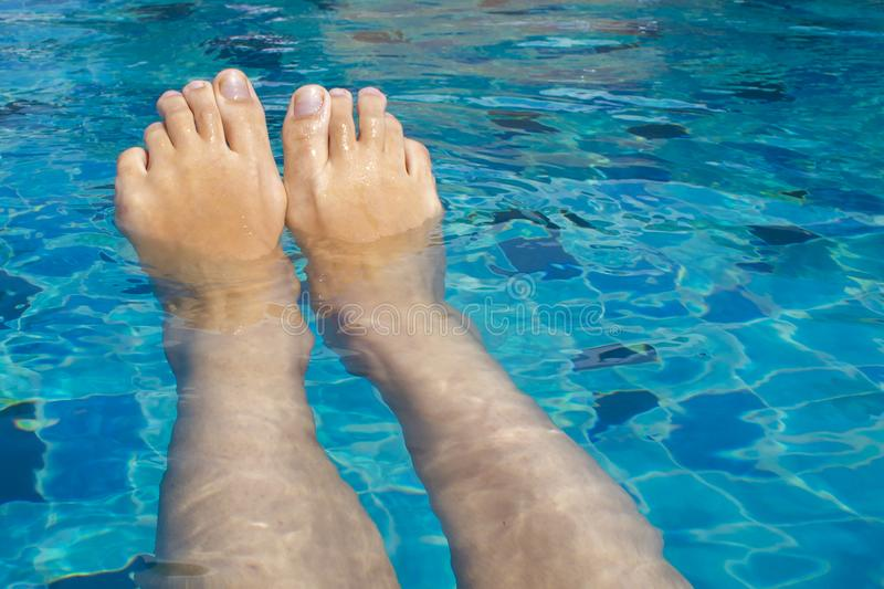 Le belle gambe femminili si rilassano in chiara acqua fotografia stock libera da diritti