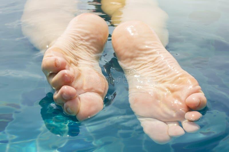 Le belle gambe femminili si rilassano in chiara acqua fotografie stock libere da diritti