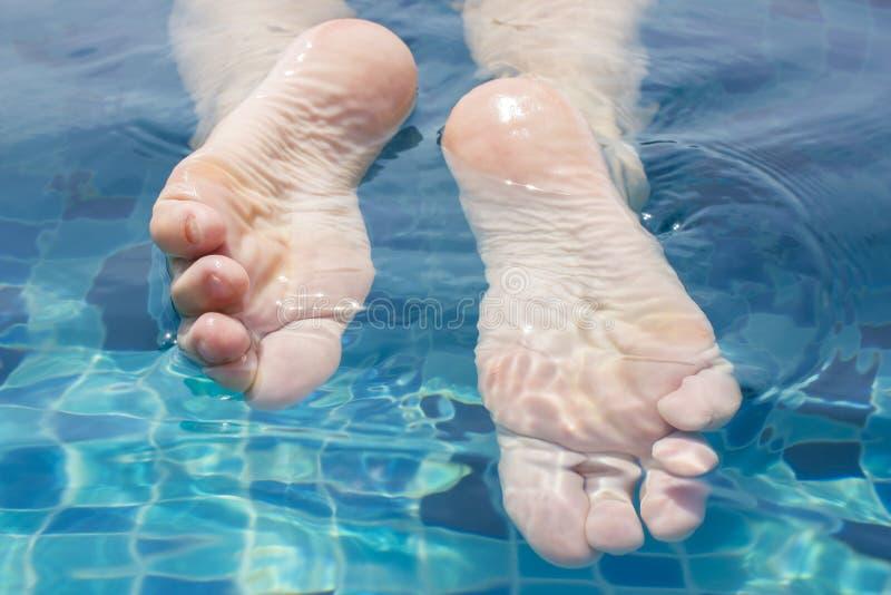 Le belle gambe femminili si rilassano in chiara acqua fotografie stock