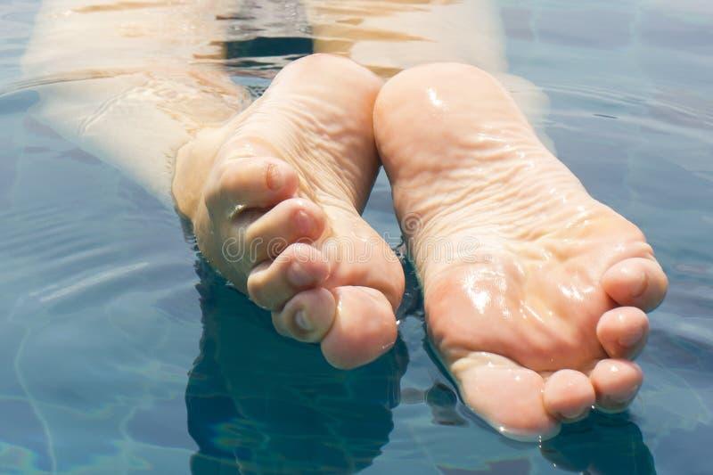 Le belle gambe femminili si rilassano in chiara acqua immagini stock libere da diritti