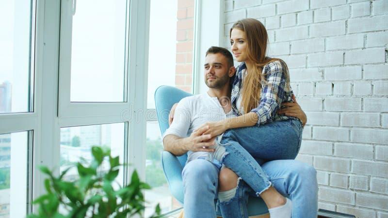 Le belle giovani coppie si rilassano la seduta sulla sedia e godere della vista dal balcone di nuovo appartamento del sottotetto immagini stock libere da diritti