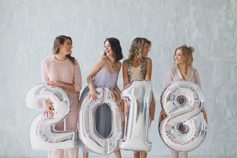 Le belle giovani donne che tengono l'argento 2018 firmano i palloni e sorridere alla macchina fotografica Partito del nuovo anno fotografia stock libera da diritti