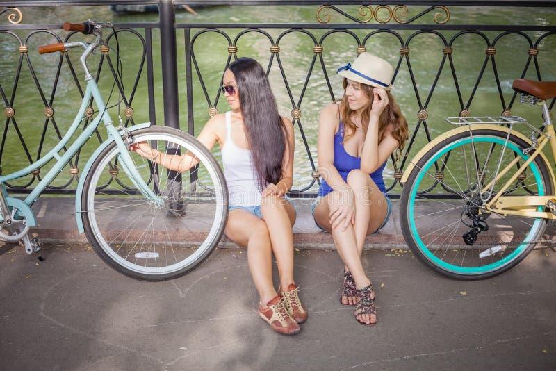 Le belle giovani donne si sono vestite nel viaggio del vestito elegante in bicicletta immagini stock libere da diritti