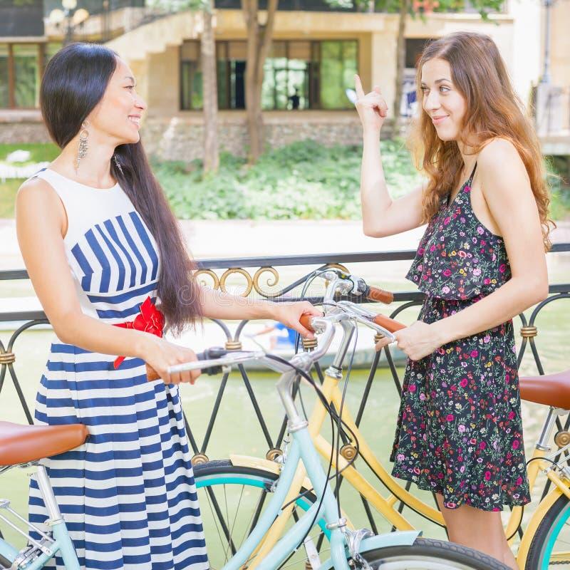 Le belle giovani donne si sono vestite nel viaggio del vestito elegante in bicicletta fotografia stock