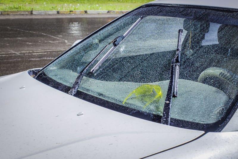 le belle gocce dell'acqua sul parabrezza dell'automobile con i pulitori di vetro hanno acceso, durante un temporale e la pioggia  fotografie stock libere da diritti