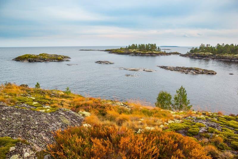 Le belle isole della roccia del lago abbelliscono Rusty Grass rosso e Moss Autumn Scenery Heavy Blue Sky verde immagini stock