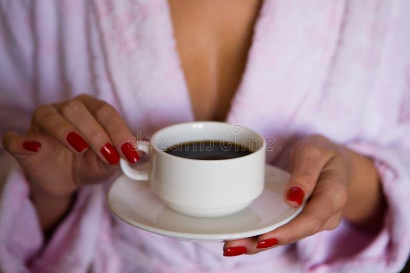 Le belle mani femminili tengono una tazza e un piatto fotografia stock