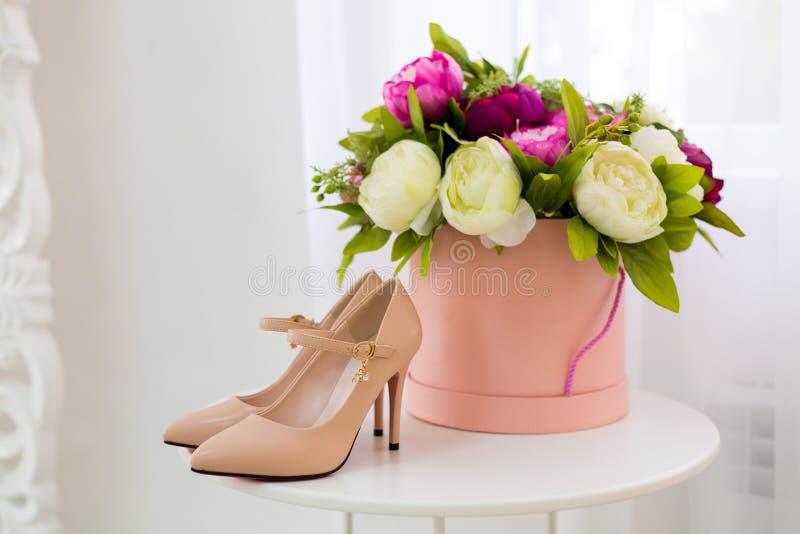 Le belle scarpe con i tacchi alti e beige sono su un tavolo bianco, accanto a una scatola rotonda con peoncini colorati fotografie stock libere da diritti