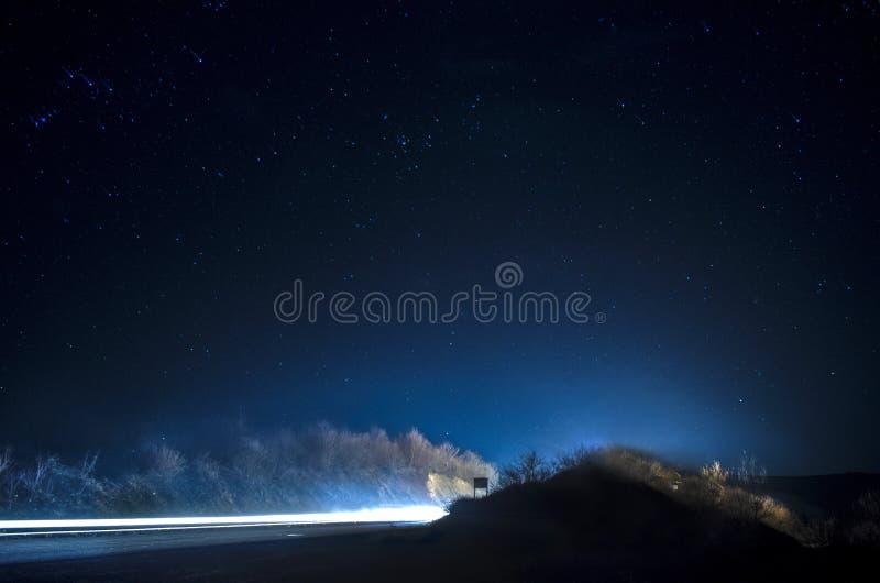 Le belle stelle su cielo notturno vicino alla strada con l'automobile accendono le piste fotografia stock libera da diritti