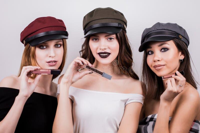Le belle tre donne con trucco ed in cappucci annunciano il rossetto, lucentezza del labbro Bellezza, modo, modo, prodotti dei cos fotografie stock