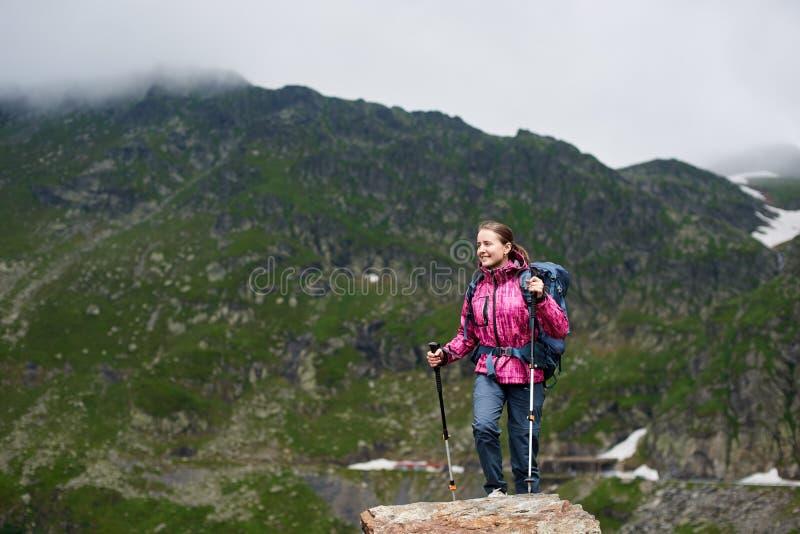 Le berg för gräsplan för fotvandrarekvinnaklättring steniga arkivfoto