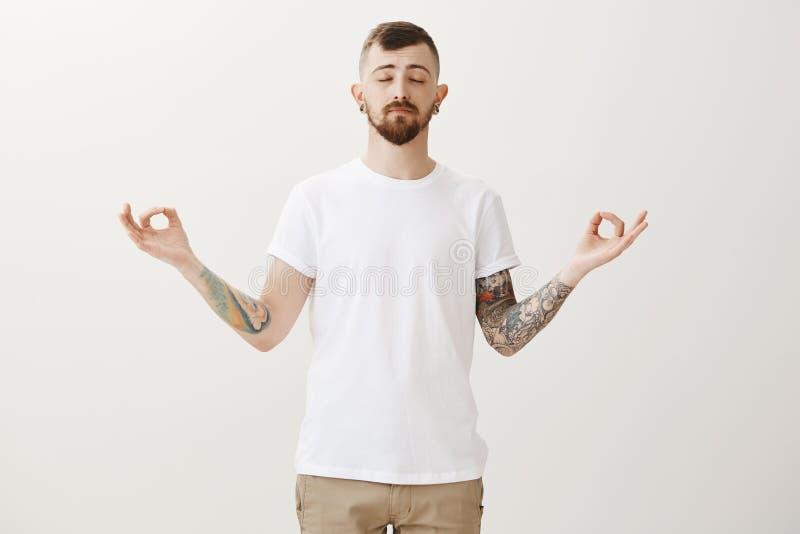 Le besoin de s'arrêter et calmer vers le bas Portrait de type urbain beau décontracté avec les tatouages et la barbe, yeux ferman photos stock