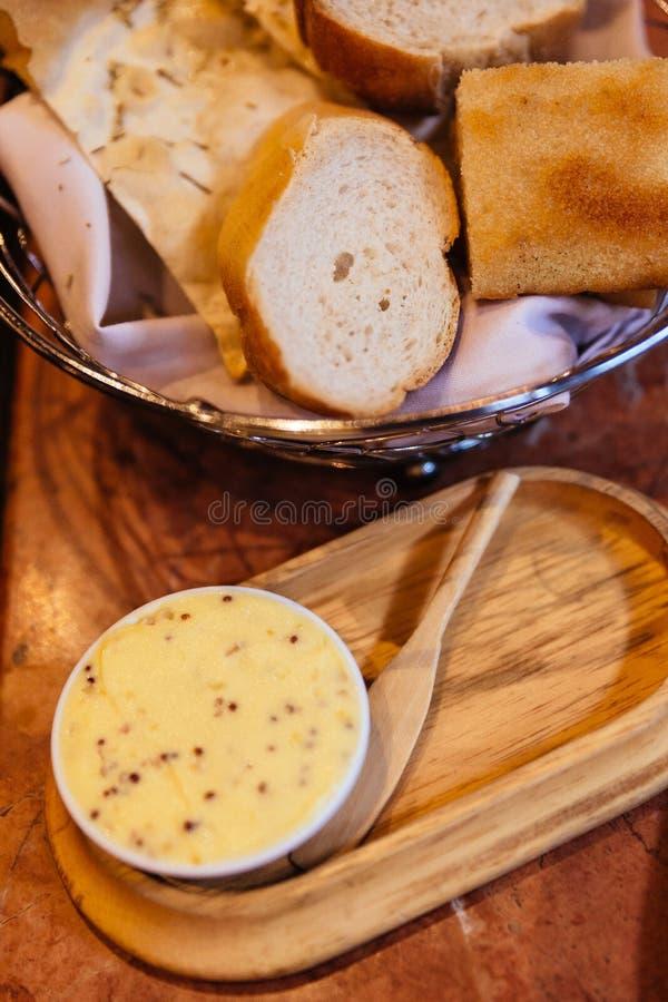 Le beurre italien dans la tasse blanche a servi avec du pain cuit au four frais dans le panier photographie stock libre de droits