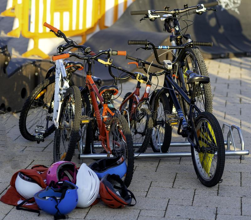 Le biciclette dei bambini hanno parcheggiato nello scaffale e nei caschi multicolori r immagine stock