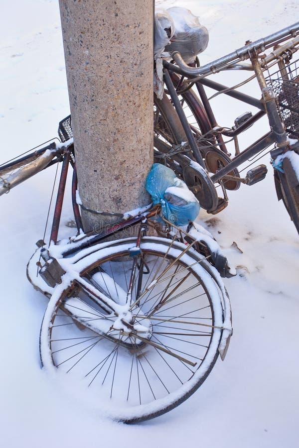Le biciclette innevate hanno parcheggiato contro una colonna, Chang-Chun, Cina fotografie stock libere da diritti