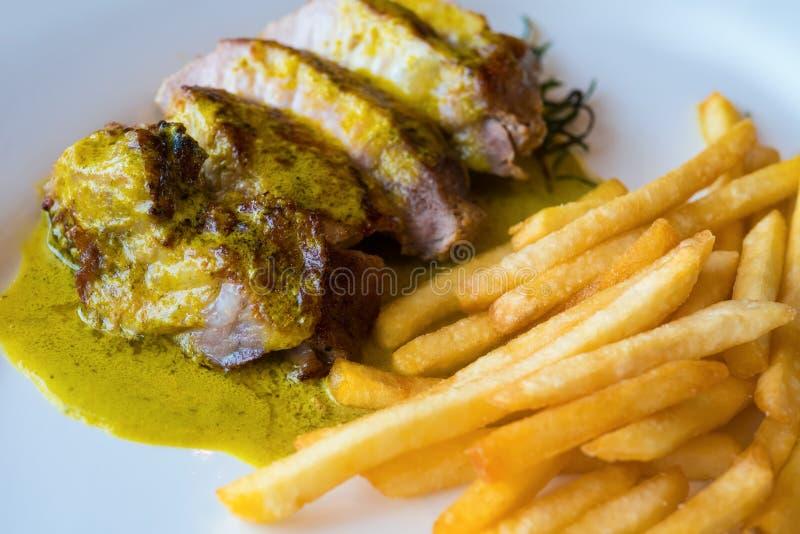 Le bifteck d'aloyau grillé de porc a servi avec de la sauce à cari et des pommes frites images libres de droits