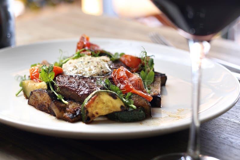 Le bifteck d'entrecôte avec le beurre persillé et les légumes grillés a servi avec un verre de vin rouge photo libre de droits