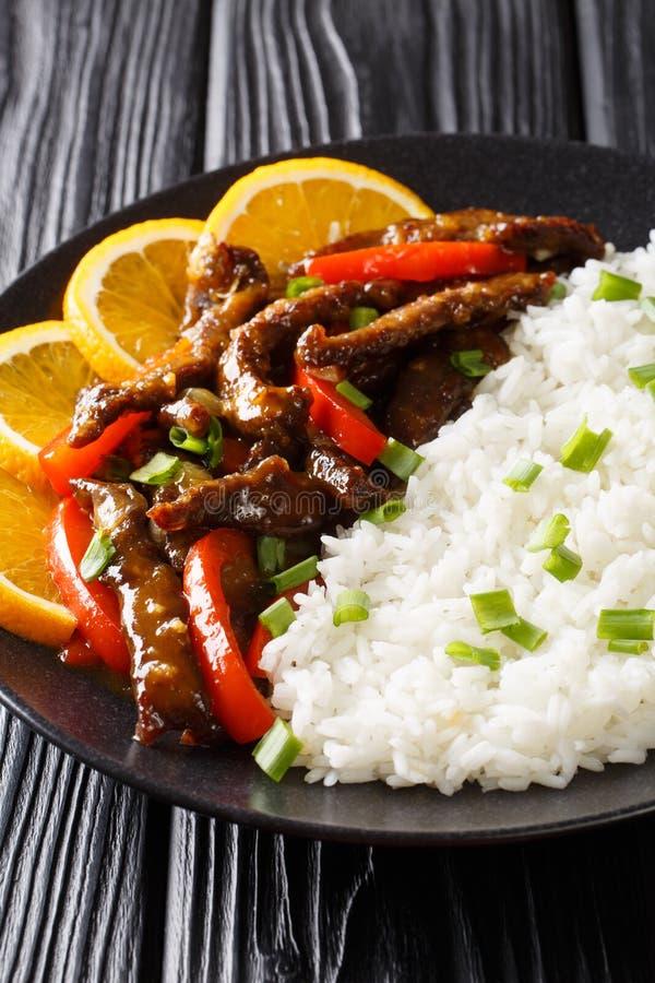 Le bifteck de boeuf coupé en tranches frit avec le paprika en sauce orange à soja a servi avec le plan rapproché de riz vertical photos stock