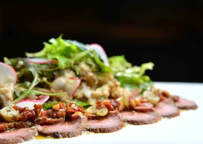 Le bifteck de boeuf grillé coupé en tranches avec le vert laisse la salade sur le plat rustique avec le radis Bifteck rare moyen  photos libres de droits
