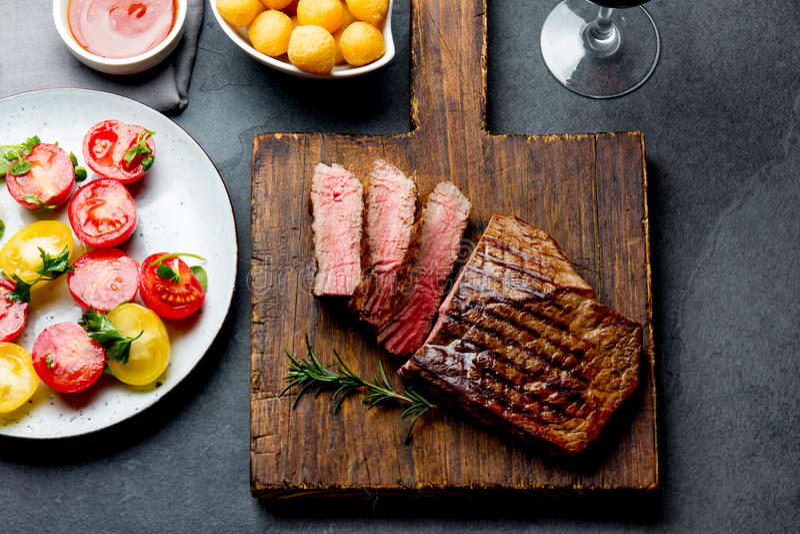 Le bifteck de boeuf rare moyen grillé coupé en tranches a servi sur le barbecue de conseil en bois, filet de boeuf de viande de B photographie stock libre de droits