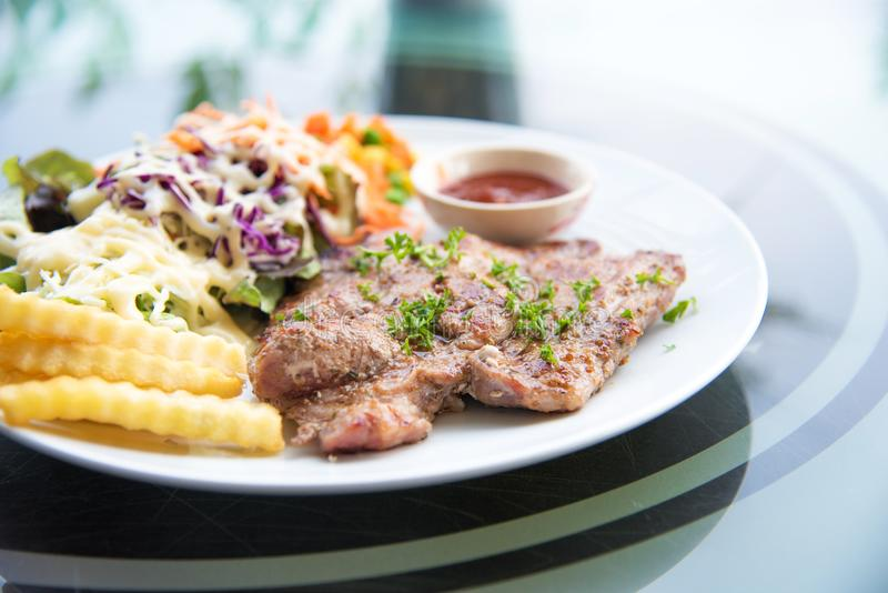 Le bifteck de côtelette de porc avec de la salade et la sauce au jus sauce dans le plat Nourriture et Veg images stock