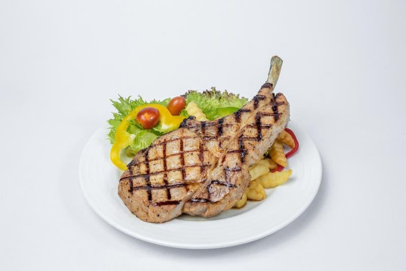 Le bifteck de côtelette de porc a servi avec de la salade fraîche et le français frits photographie stock