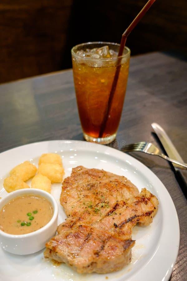 Le bifteck de porc avec de la sauce au poivre a servi avec les pommes de terre rissolées sur le wh photographie stock libre de droits