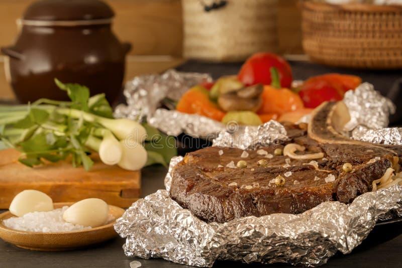 Le bifteck de viande a fait cuire au four dans l'aluminium et les l?gumes cuits au four sur une table en bois avec les tomates fr photographie stock
