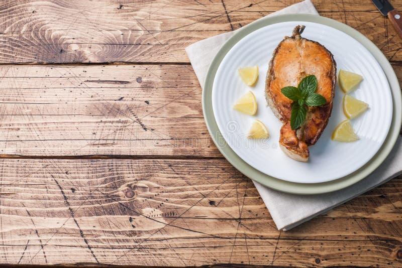 Le bifteck a fait des saumons cuire au four de poissons d'un plat avec le citron Table en bois photo stock