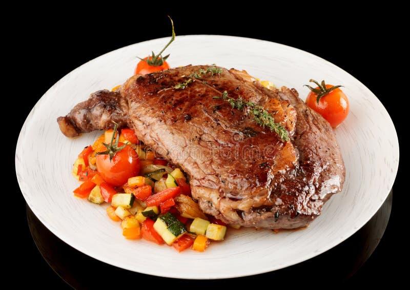 Le bifteck savoureux de ribeye avec l'émoi a fait frire des légumes d'isolement sur le noir photo stock