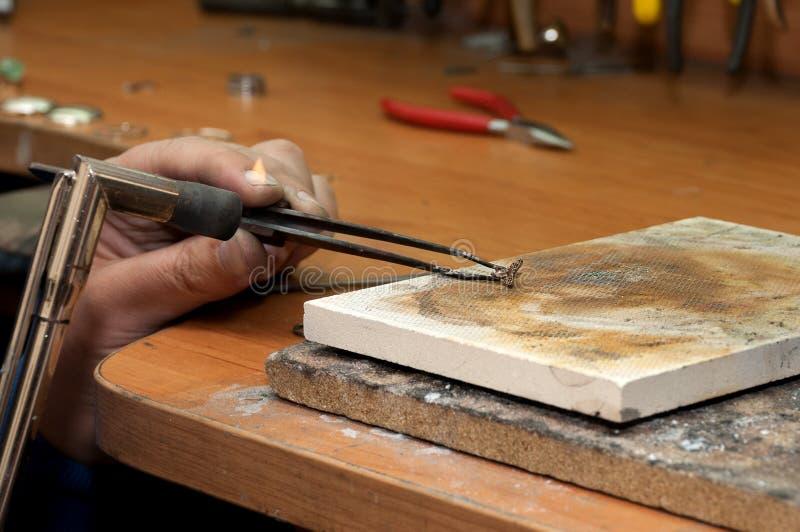 Le bijoutier chauffe l'objet d'un anneau sur une pierre image libre de droits