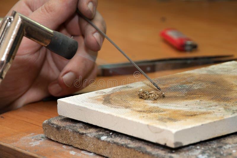 Le bijoutier traite l'objet de l'anneau photos stock