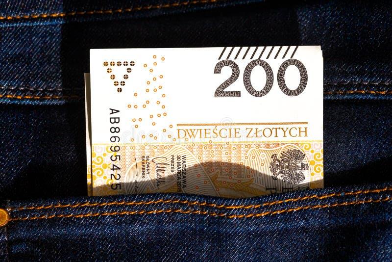 le billet de banque de 200 zloty dans des jeans empochent Fin vers le haut images libres de droits