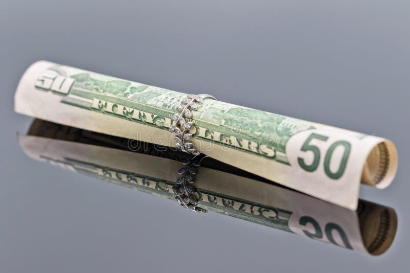 Le billet de cinquante dollars est roulé dans l'anneau d'argent du ` s de femmes élégantes photo libre de droits