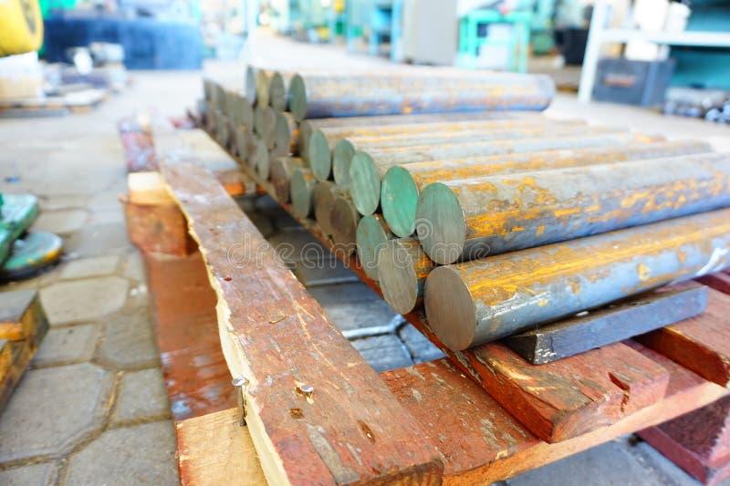 Le billette del ferro sono in azione e aspettano per lavorare sulle macchine utensili, un magazzino dei prodotti siderurgici fotografia stock libera da diritti