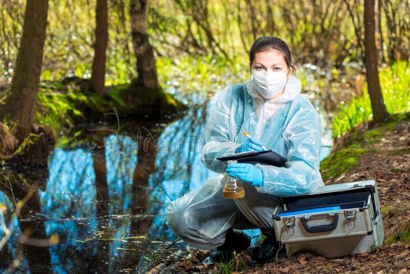 le biologiste prend l'eau d'une rivière de forêt pour étudier la composition photo stock
