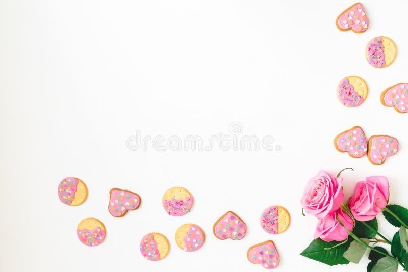 Le biscuit de pain d'épice avec le lustre rose et les roses fleurissent sur le fond blanc Configuration plate Vue supérieure Fond photo libre de droits